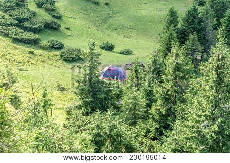 Tourist Tent In The Mountains. Tourists In The Mountains. A Tent Among The Trees.