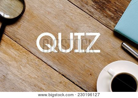 Top View Of A Cup Of Coffee,magnifying Glass,notebook And Pen On Wooden Background Written With Quiz