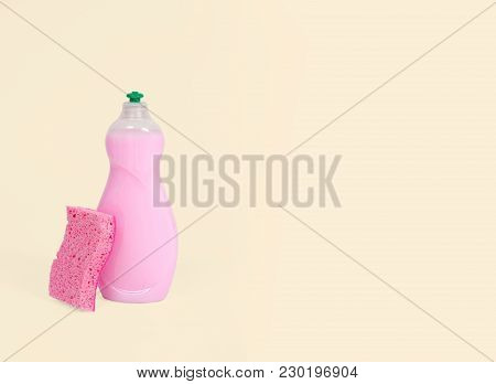 Detergents And Sponge For Dishes On Pastel Yellow Background
