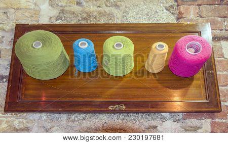 Five Colourful Yarn Bobbins On A Display Board.
