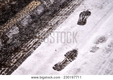 Car Tracks And Shoe Footprints In Snow On Icy Winter Asphalt Road.