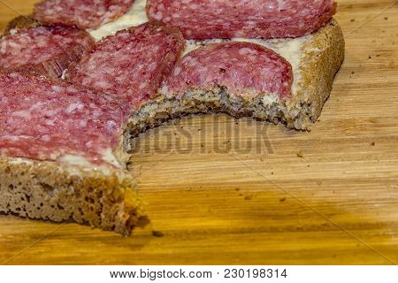 A Bitten Slice Of Salami. Lean Breakfast. Bitten Sandwich. Close Up