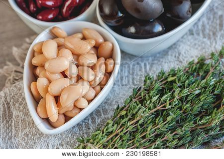 Beans Are White And Red With Large Black Olives In White Small Cups With Green Leaves Of Arugula And