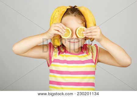 Cheerful little girl with a lemon and banana  in studio