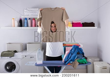 Woman Looking At Burned Cloth While Standing By Ironing Board In Laundry Room