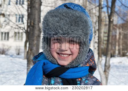 A Small A Boy Winter Sunlight A Day To Looks At Us And Smiles. On The Street White Snow. A Boy A Sat