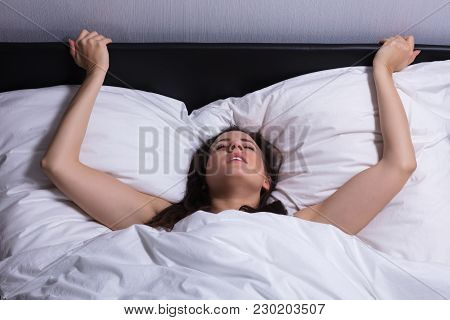 High Angle View Of A Young Woman In Bed Getting Orgasm