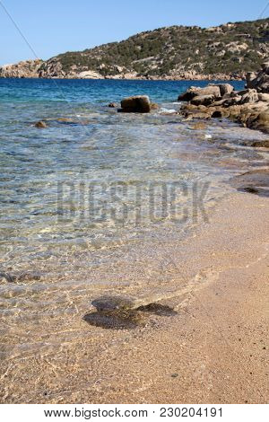 a view of the clear water of the Mediterranean sea in a quiet beach in the coast of Baja Sardinia, in the famous Costa Smeralda, Sardinia, Italy