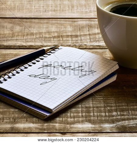 closeup of a notebook with the text poetry day written in it, a pen and a cup of coffee on a rustic wooden table