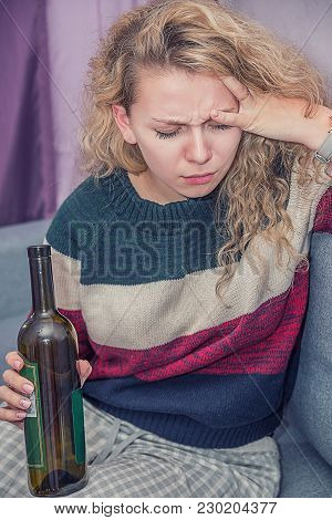 A Young Girl Drinks Alcohol, Wine From A Bottle, With Disheveled Hair, She Is Sad And Offended Becau