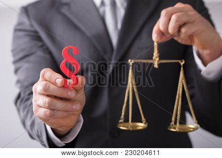 Judge Holding Paragraph Symbol And Justice Scale