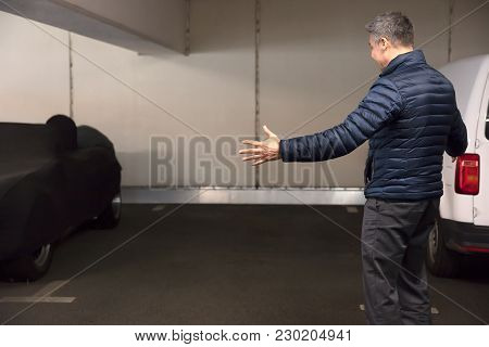 Rear View Of A Shocked Man Standing In Parking Lot After His Car Was Stolen