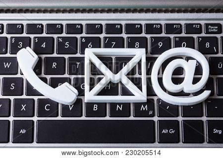 Contact Methods. Elevated View A Phone, Email And Post Icon On Laptop Keypad