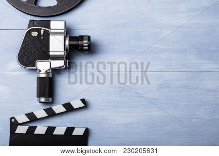High Angle View Of Movie Camera With Film Reel And Clapper Board On Wooden Plank