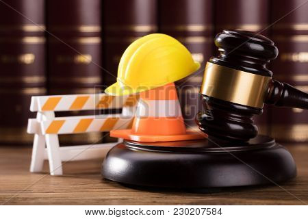 Close-up Of Mallet With Road Barrier, Yellow Hard Hat And Traffic Cone In Courtroom