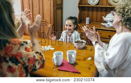 Little Girl Winning Domino Her Mother And Her Grandmother