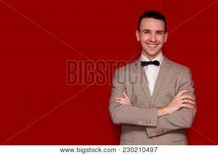 Portrait Of Smiling Handsome Stylish Man In Elegant White Suit On Red Background. Business Style. Fa