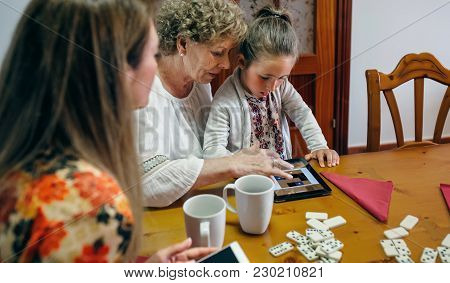 Grandmother And Granddaughter Play A Game On The Tablet While The Mother Watches