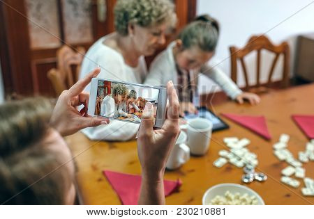 Grandmother And Granddaughter Play A Game On The Tablet While The Mother Takes A Photo With The Smar