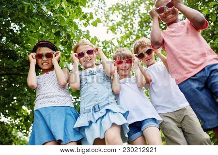 Cool interracial group of kids with sunglasses in summer holidays