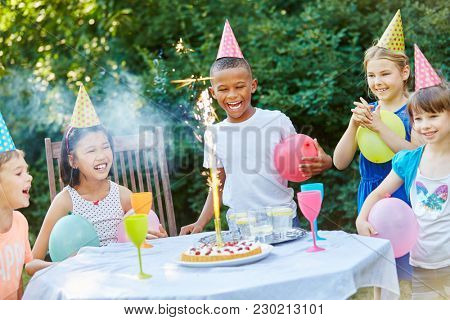 Kids celebrating together birthday party with table fireworks on cake