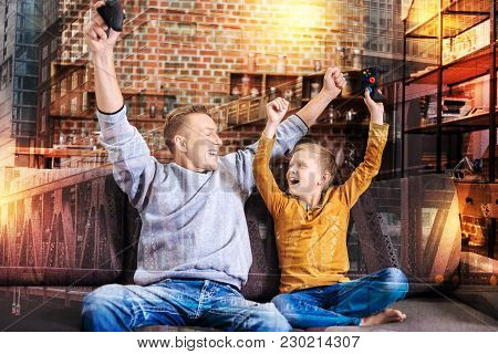 Victory. Cheerful Emotional Young Man Feeling Excited And Looking At His Happy Smiling Son While Hol
