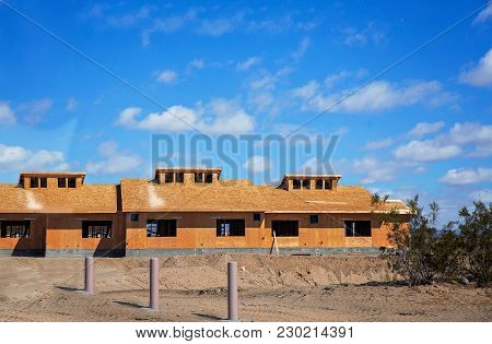 Three Apartment Homes Under Construction With A Wood Frame Under A Blue Cloudy Sky