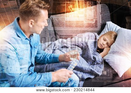 Ill Child. Tired Little Boy Feeling Unwell And Sleeping While His Kind Loving Worried Father Sitting