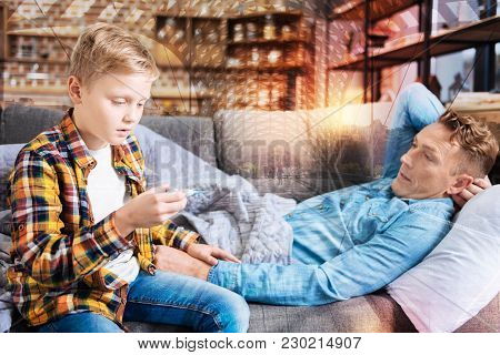Surprised Child. Serious Attentive Boy Feeling Worried While Sitting Next To His Ill Father On A Sof