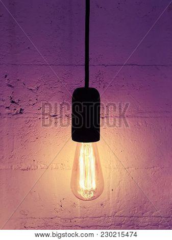 Industrial Design Light Bulb On A Black Cord. Warm Purple Light.