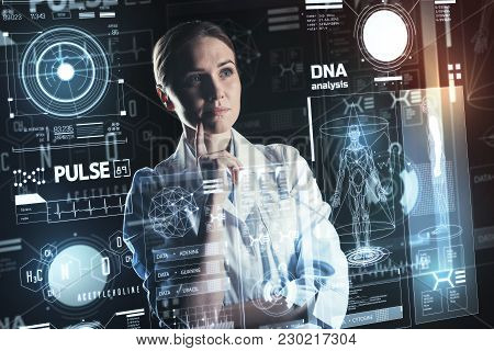Dna Analysis. Smart Calm Experienced Doctor Standing With Her Fingers Touching Her Chin And Thoughtf