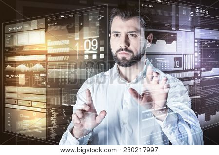 Attentive Employee. Calm Attentive Concentrated Programmer Looking Serious While Standing In Front O