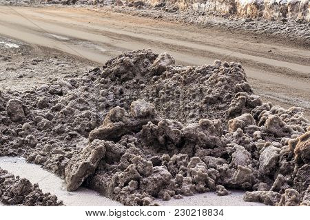 Piles Of Dirty Snow On The Streets Of The City In Siberia. Sand And Reagents Against Icy Condition.