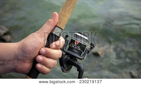 Fishing Reel Closeup. Man Is Fishing With Spinning Fishing Rod Close To Coast Shore Line. Outdoor Re