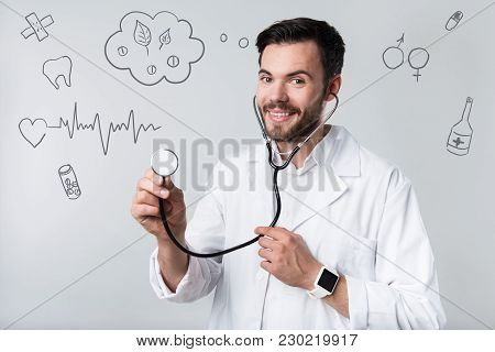 Reliable Doctor. Experienced Reliable Young Doctor Looking Calm And Friendly While Standing With A M