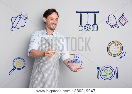 Professional Chef. Skilled Experienced Handsome Chef Looking Happy While Standing In A Kitchen And H