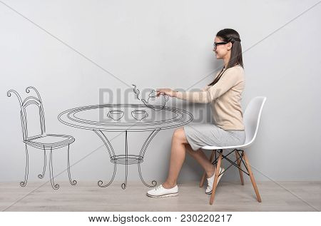 Tea Time. Creative Young Elegant Woman Sitting On A White Chair And Feeling Excited While Dreaming O