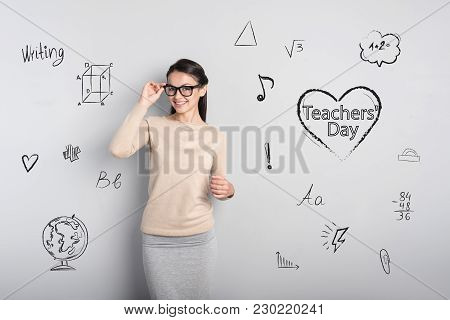 Cute Teacher. Clever Kind Beautiful Teacher Touching Her Glasses And Smiling While Being In A Good M