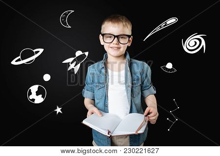 Curious Boy. Clever Cheerful Curious Boy Wearing Big Glasses And Feeling Glad While Holding A Big No