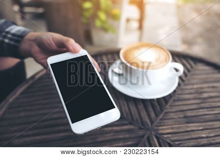 Mockup Image Of A Hand Holding And Giving White Mobile Phone With Blank Black Desktop Screen To Some