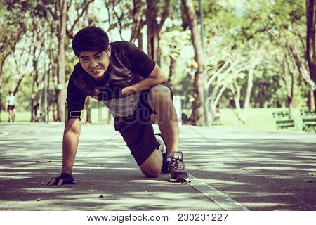 Asian Man Has A Heart Pain While Exercising In A Park.