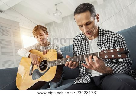 I Like Playing. Attractive Concentrated Little Fair-haired Holding The Guitar And His Father Teachin