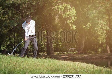 Asian Man Golf Player Swinging Driver Golf Club On Golf Course.