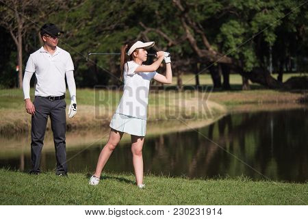 Asian Young Couple Playing Golf On Golf Course, The Male Partner Is Trainer To The Female Golfer