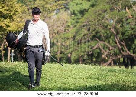 Portrait Of Asian Young Male Golfer With Golf Club Bag On The Golf Course.