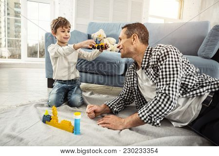 My Favourite Toy. Nice Cheerful Fair-haired Boy Playing With His Erector Set And His Daddy Sitting N