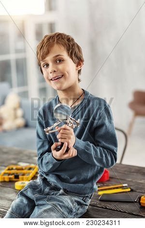 In High Spirits. Lovely Cheerful Fair-haired Boy Smiling And Holding A Magnifying Glass While Sittin