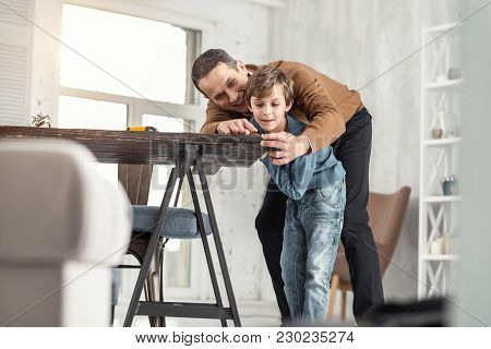 Loving Father. Nice Exuberant Little Fair-haired Boy Holding A Measuring Tape And Measuring The Tabl