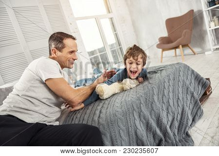 Having Fun. Nice Exuberant Fair-haired Boy Laughing And Lying On The Bed And His Daddy Playing With