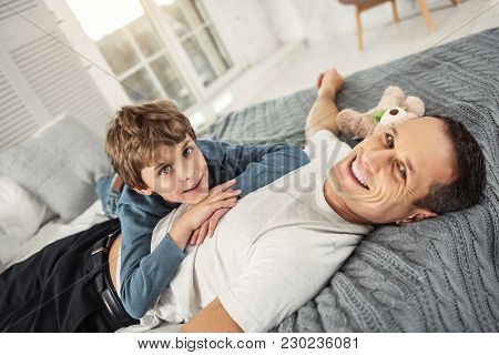 My Dear Daddy. Nice Cheerful Fair-haired Boy Smiling And His Daddy While Lying On His Back On The So